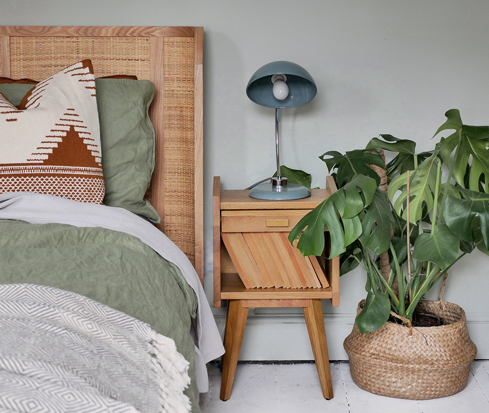 The corner of a bed and bedside table in a green boho bedroom with large house plant