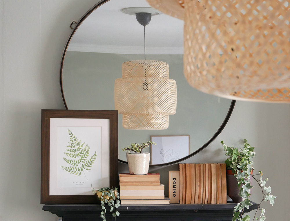 Styled shot of a fireplace mantlepiece in a bohemian inspired bedroom with vintage paperbacks and large round mirror