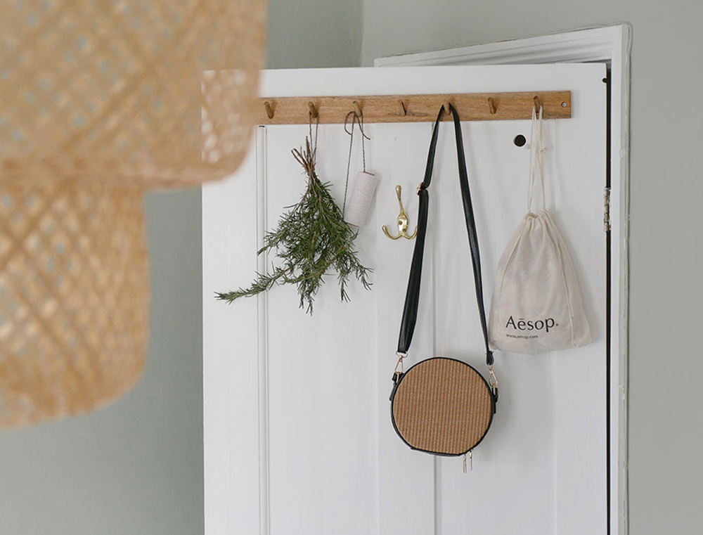 White painted door with oak hooks and hanging bunches of dried herbs,in a boho bedroom