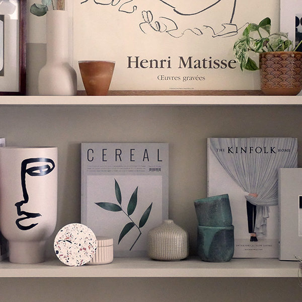 shelves decorated with neutral toned objects including a vase with an abstract face print