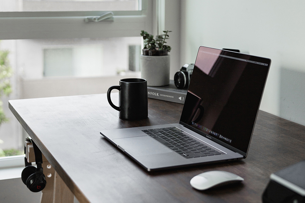 A laptop sits on a dark wooden desk near a window with bright sunlight