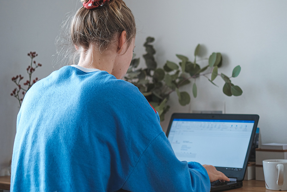 A woman has her back to the camera while working on a laptop with a vase of eucalyptus in the background