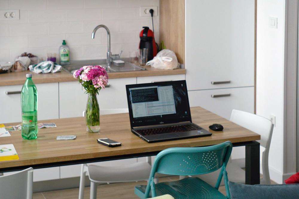 A laptop is open on a dining table with a kitchen in the middle ground