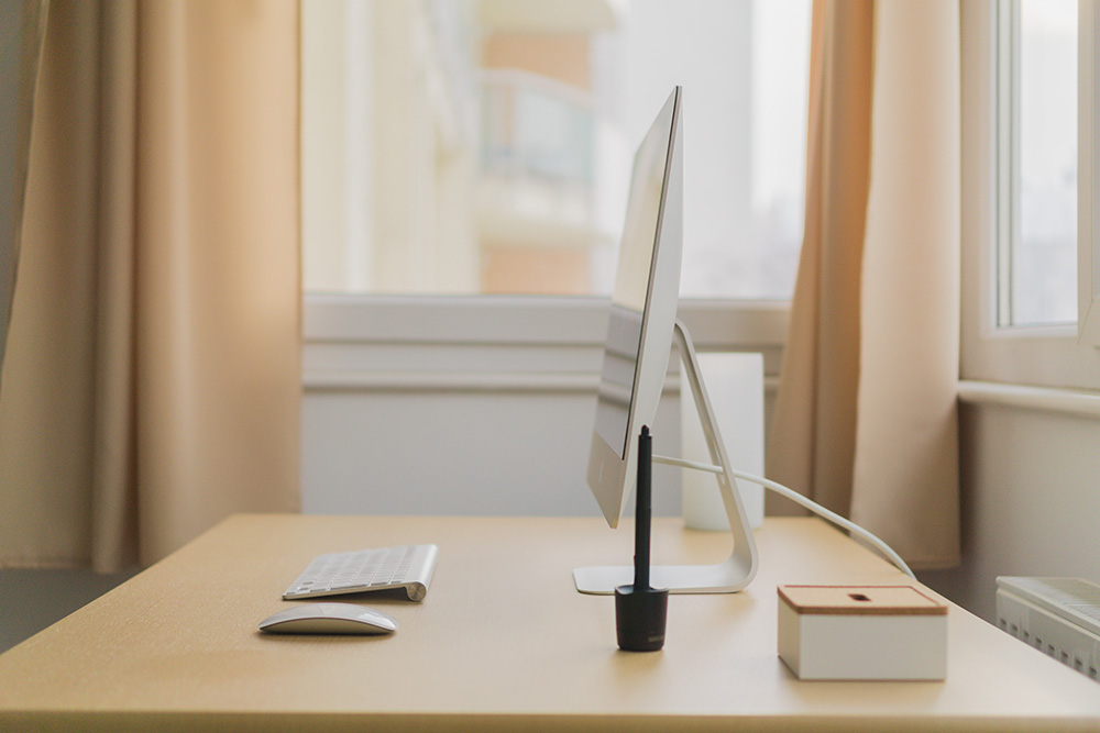 A side profile of an iMac on a clean desk set up with neutral coloured curtains in the background
