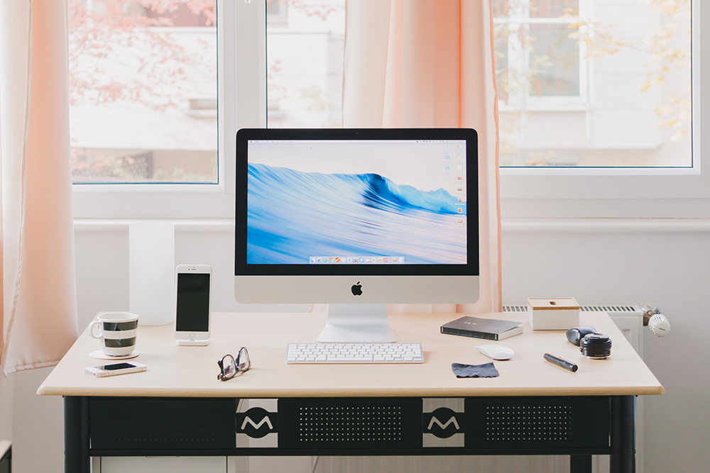 A clean and peach-coloured office set up with iMac and pine wood desk