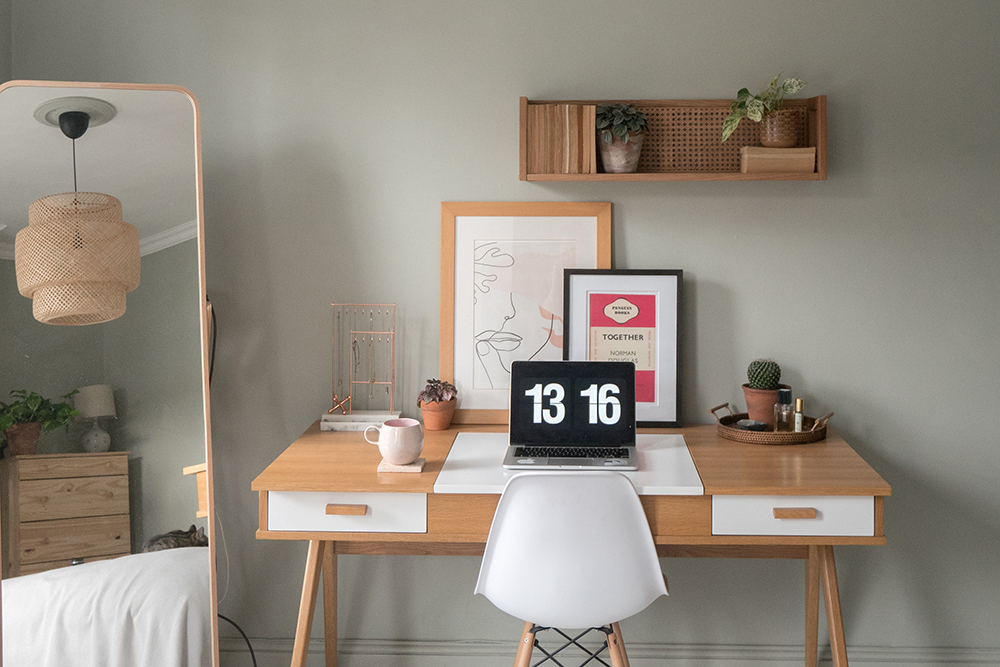 Office corner of a boho bedroom with desk, full length mirror and laptop
