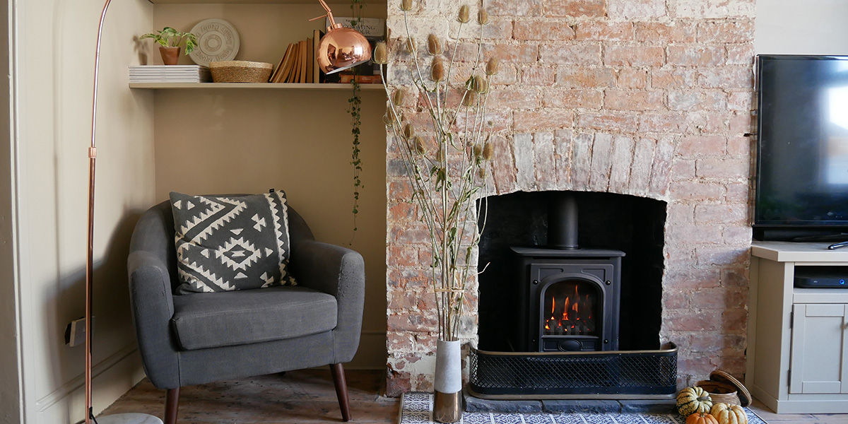 exposed brick chimney breast with wood burning stove lit in a neutral-painted living room