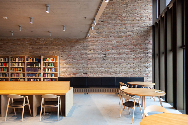 a large gallery space with one double height wall in bare brickwork