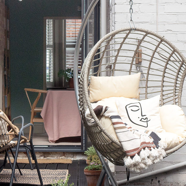 hanging egg chair on a dark garden deck