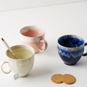 three mugs styled with teaspoon and biscuits