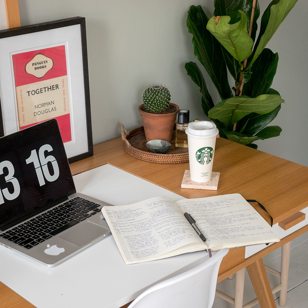 laptop and open notebook on desk next to a takeaway coffee cup