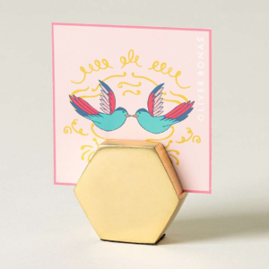gold hexagonal desktop photo or note holder with a postcard in it