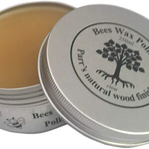 Opens silver tin of beeswax with a tree design