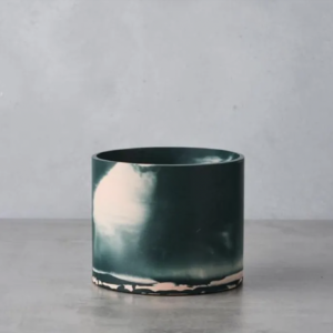 Forest green and pink cylindrical vase on a concrete surface