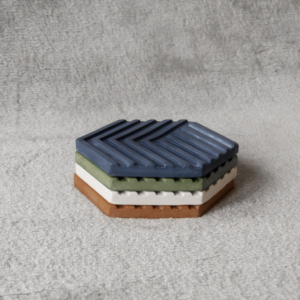 A stack of 4 jesmonite coasters in a hexagonal design, in warm autumnal colours