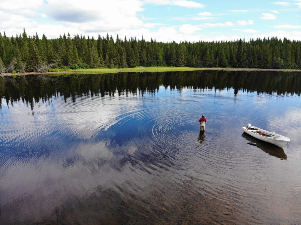 Fly Fisherman wading by his boat - fishing for trout and Arctic char at Skålestrømmen, Norway