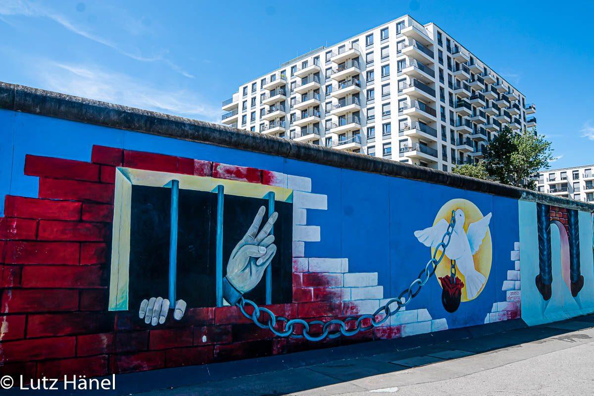 Foto zeigt die Bebauung des Todesstreifen der Berliner Mauer hinter der East Side Gallery wofür extra Mauerelemente versetzt wurden.
