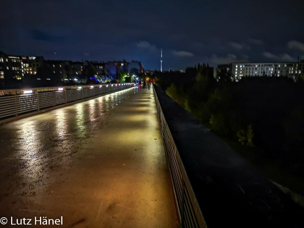 bei Nacht im Regen der Beleuchteter Schwedtersteg