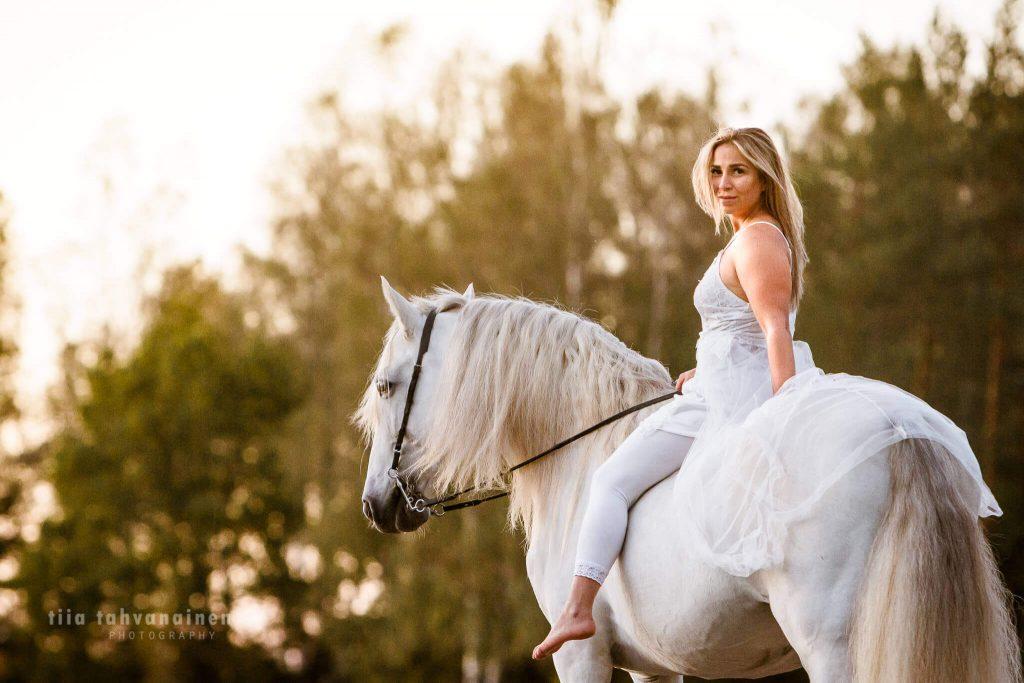 Kimo pura raza española-ori (andalusialainen) valkoiseen mekkoon pukeutunut omistaja selässään ilta-auringossa Ruotsissa