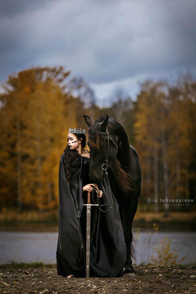 Friisiläistamma Queen Afrodite halloween-teemaisessa kuvassa mustaan viittaan, kasvomaaleihin ja kruunuun pukeutuneen mallin kanssa.