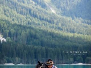 Noriker-tamma Libelle turkoosin värisessä, Dolomiittien ympäröimässä, alppijärvessä Etelä-Tirolissa, Italiassa, paikallisiin perinnevaatteisiin pukeutuneen omistajansa kanssa