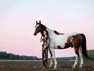 Lehmänkirjava puoliveriruuna Irys III kukkahaalariin pukeutuneen omistajansa kanssa Nummelan lentokentällä auringonlaskun värjätessä taivaan vaaleanpunaiseksi