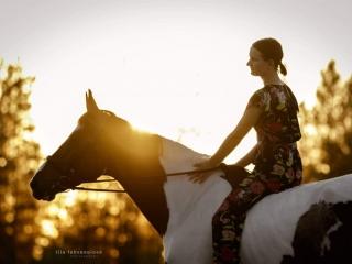 Lehmänkirjava puoliveriruuna Irys III kukkahaalariin pukeutuneen omistajansa kanssa vasten auringonlaskua