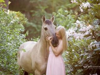 Hiirakko poni alppiruusupuistossa vaaleanpunaiseen mekkoon pukeutuneen omistajansa halauksessa