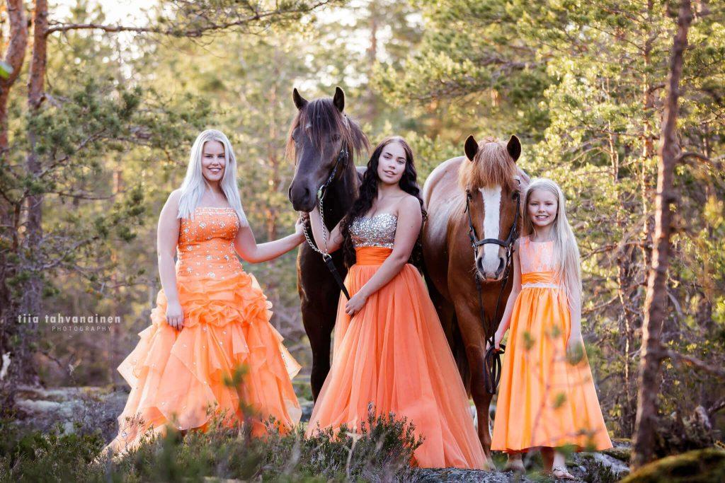 Ihana kesäinen kuva oranssiin mekkoihin pukeutuneesta sisaruskolmikosta kahden hevosen kanssa