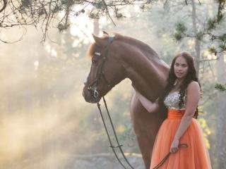 Suomenhevosruuna Usvasuon Donjuan oranssiin prinsessamekkoon pukeutuneen omistajansa kanssa kallion laella auringonsäteiden siivilöityessä usvan ja puiden läpi