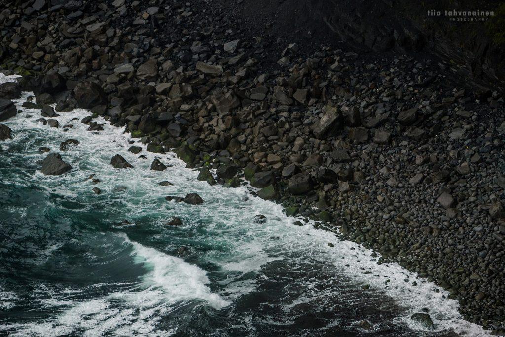 Tummasävyinen kiviranta turkoosin meriveden iskiessä rantaan Irlannin Cliff of Moherin lähistöllä