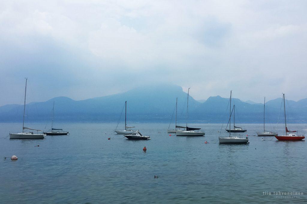 Veneitä paikallaan Garda-järvellä, Italiassa sumuisten vuorten jäädessä taustalle