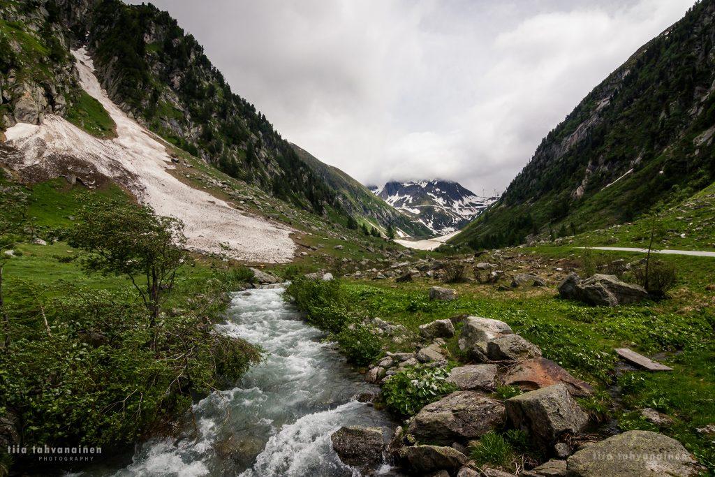 Vuoripuro vuorten reunustamassa laaksossa lumihuippuisten vuorten jäädessä taustalle Sveitsissä 2018