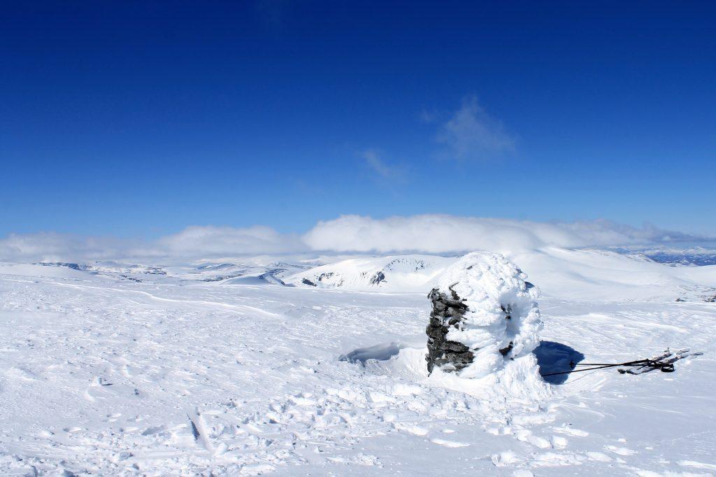 Toppvarden på Besshøe 2.258 moh, med en skudekket Glittertind i bakgrunnen.