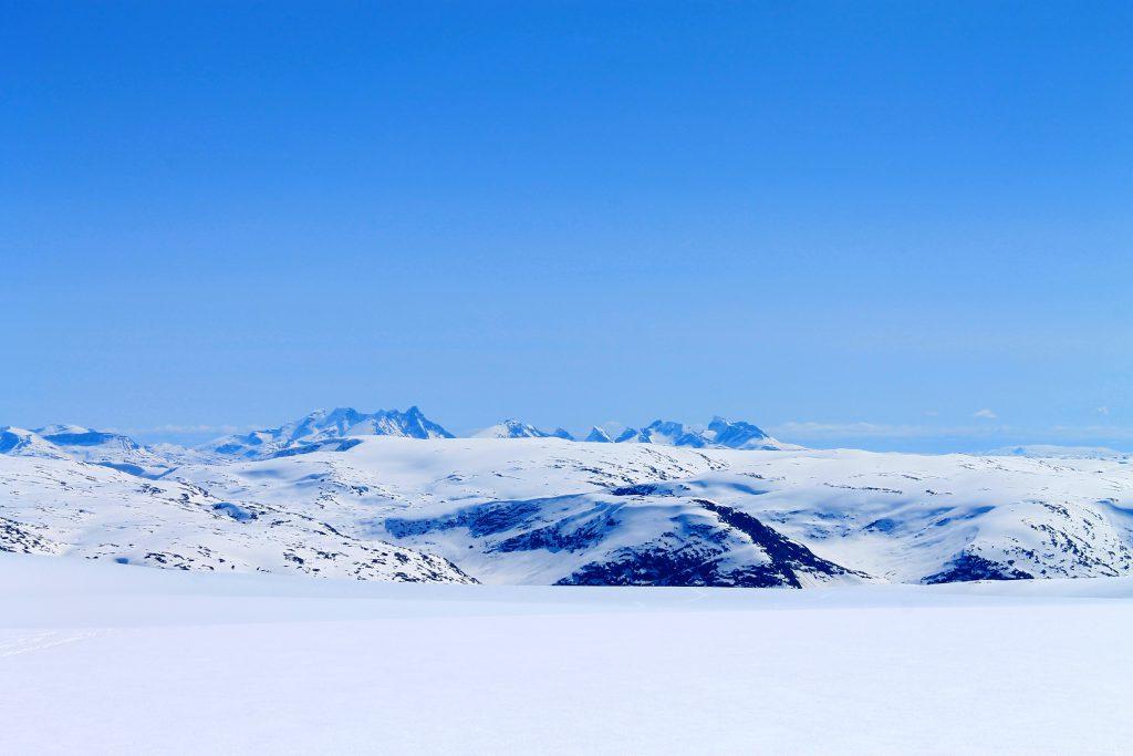 Vel oppe på Jostedalsbreen stikker Hurrungane opp i det fjerne.