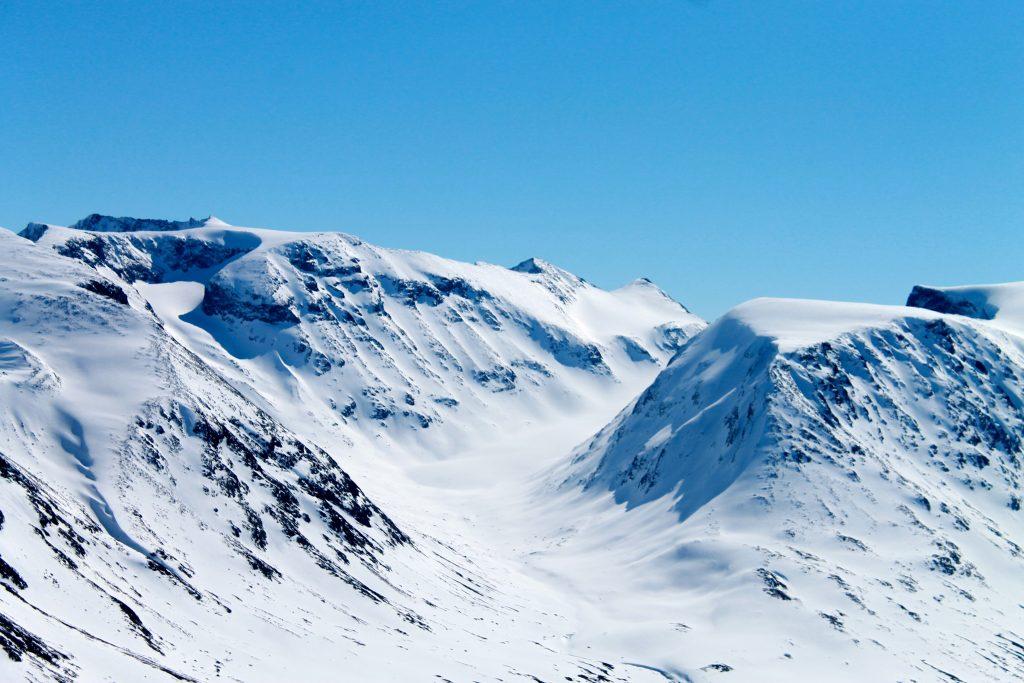 Hellstugubreean strekker seg ned dalen mellom Memurutindan til venstre og Hellstugutindan til høyre i bildet.