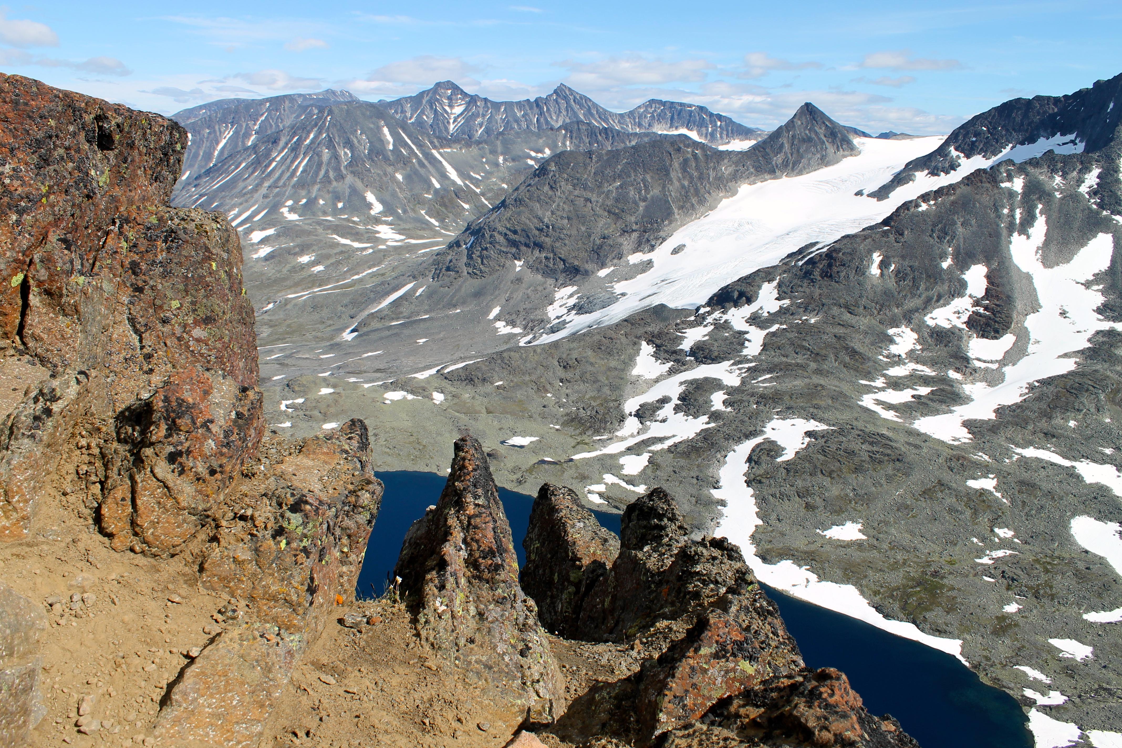Midtre og Store Hellstugutindan er de spisse tindene helt bak i bildet. Her sett fra Kyrkja.
