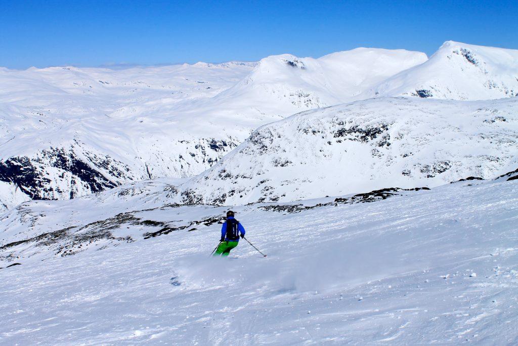 Skikjøring ned Dyrhaugsryggen med Steindalsnosi og Fannaråken i bakgrunnen.