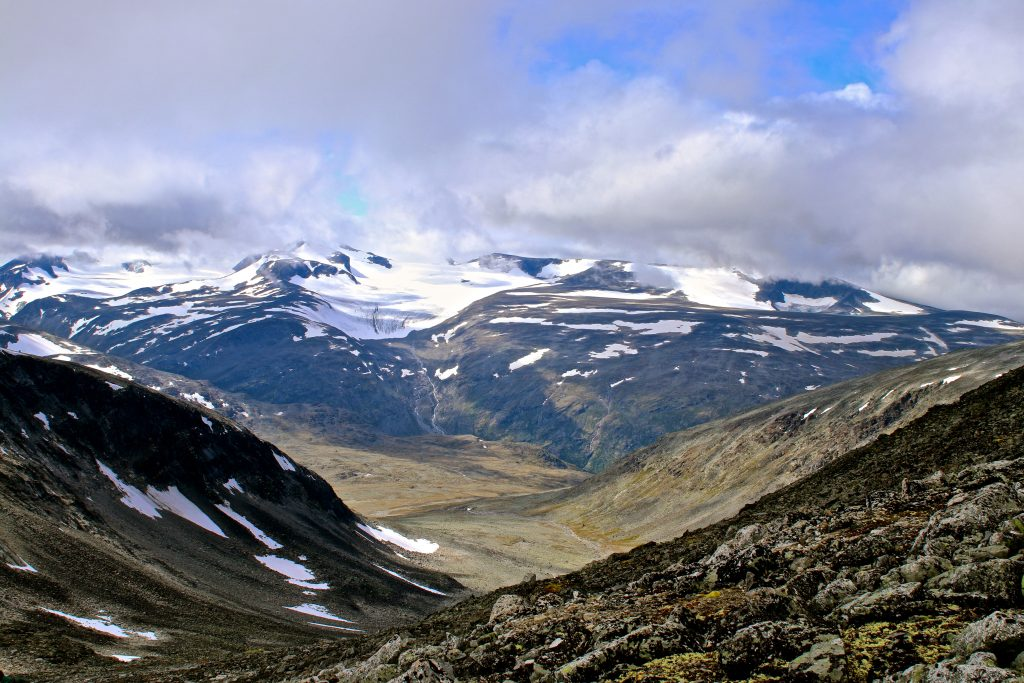 Utsikt ned i Visdalen med Svellnosbrean, Styggebrean, Vesljuvbrean og en tåkelagt Galdhøpiggen. Her sett fra Glittertinden.