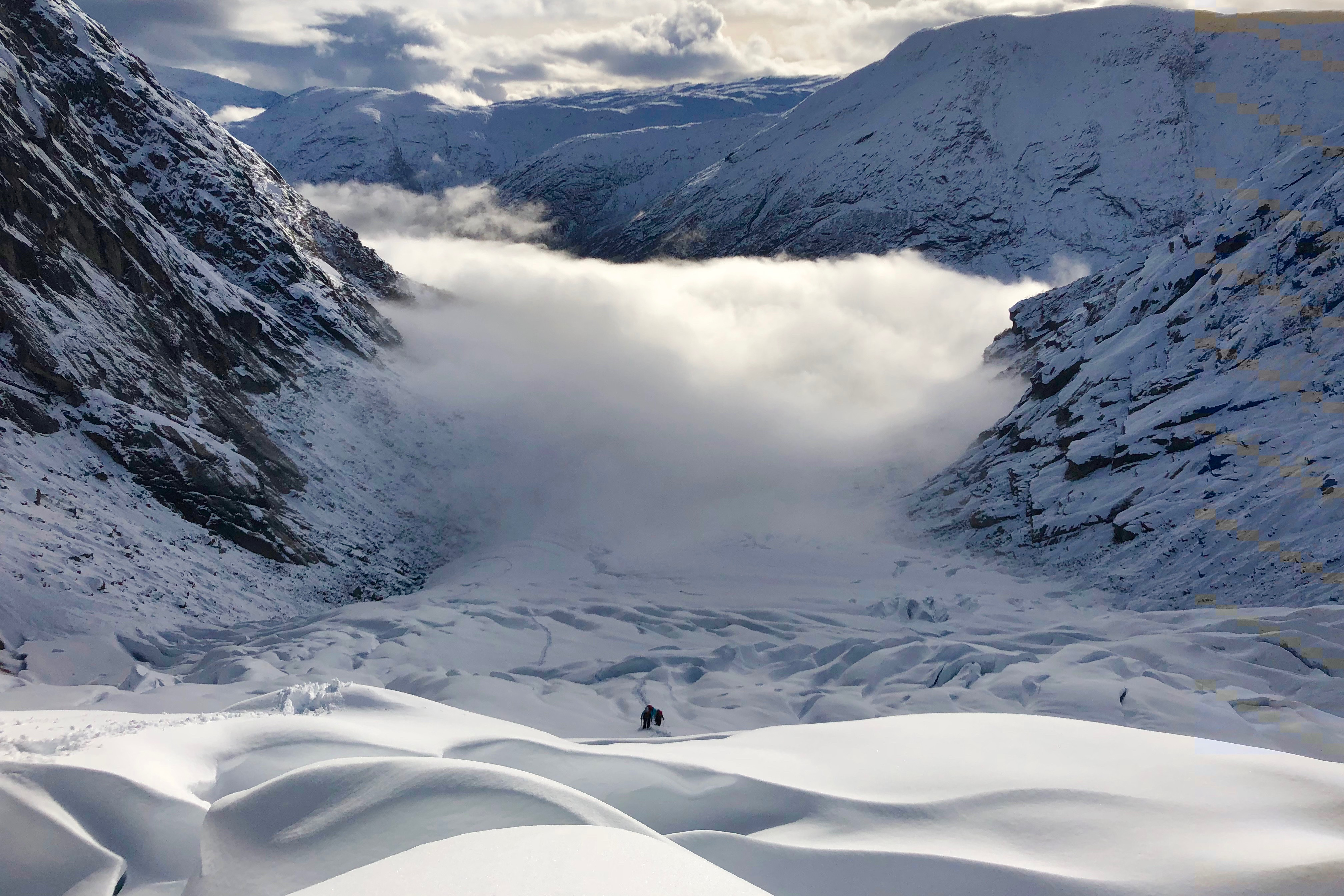 Utsikt fra Tuftebreen ned mot en tåkelagt Krundalen.