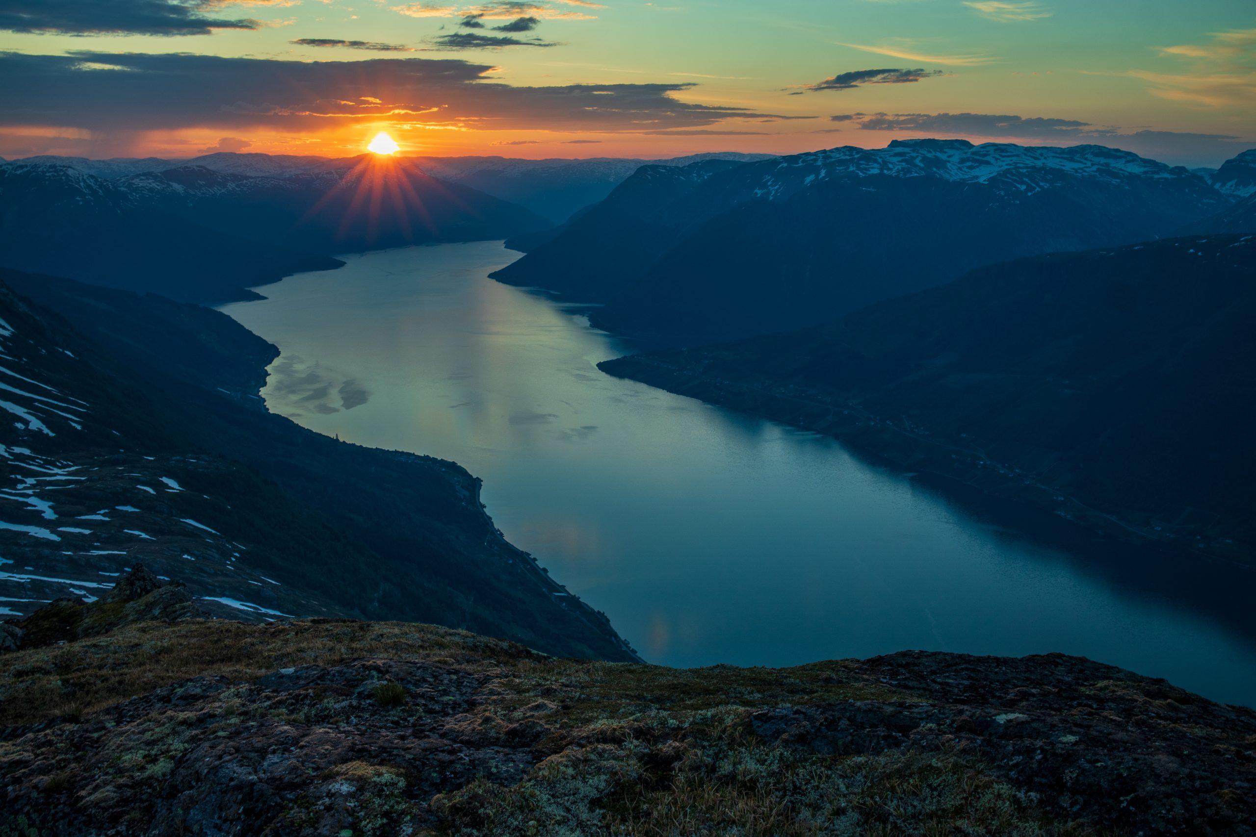Solen står opp over Vassfjøro og Midfjellet. Utsikt fra Rundenuten.