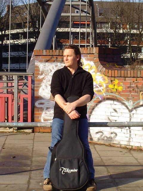 Singer Songwriter Torsten Q mit Gitarre vor einer Brücke in Hamburg Winterhude.