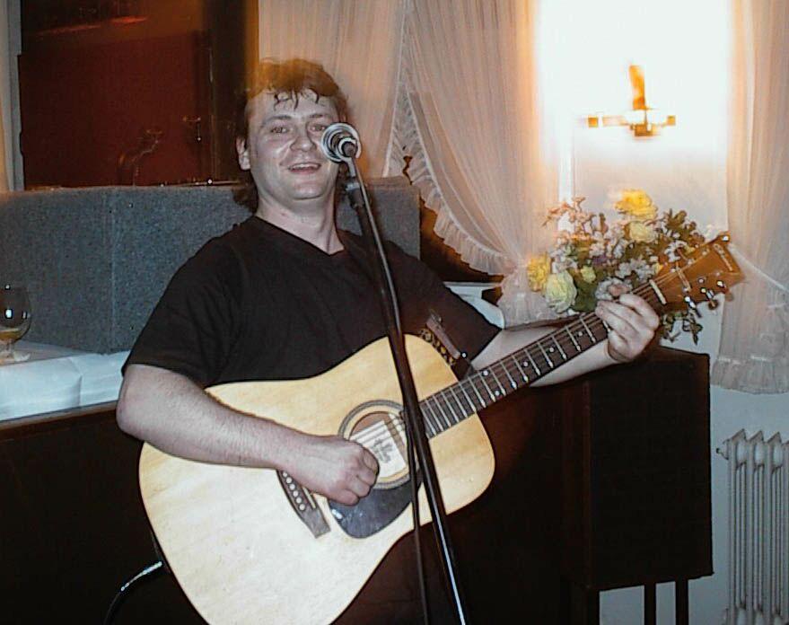 der Alleinunterhalter, Sänger und Gitarrist Torsten Q aus Hamburg mit Gitarre vor einem Mikrofonständer während eines Auftritts bei einer Hochzeit
