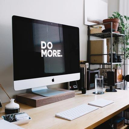 """En dator som står på ett skrivbord, på skärmen står det """"Do more"""""""