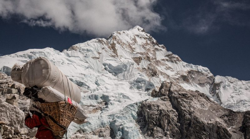 A mountain in the The Himalayas with a sherpa in front