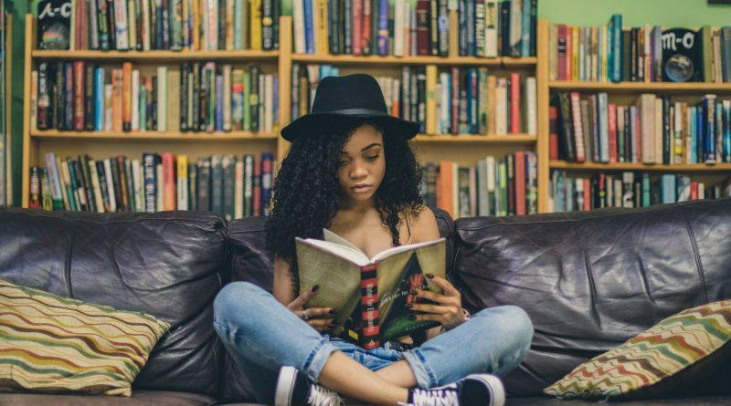 A picture of a girl reading a book in the library
