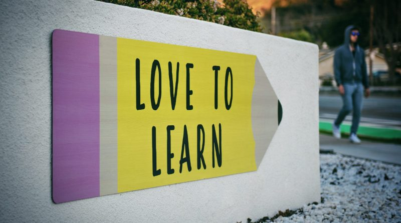 A sign in purple, yellow, and grey with the words: Love to Learn.