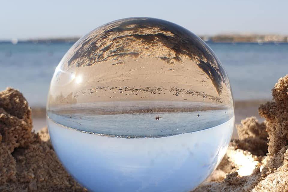 egypte zon, zand en zee gezien door een glazen bol