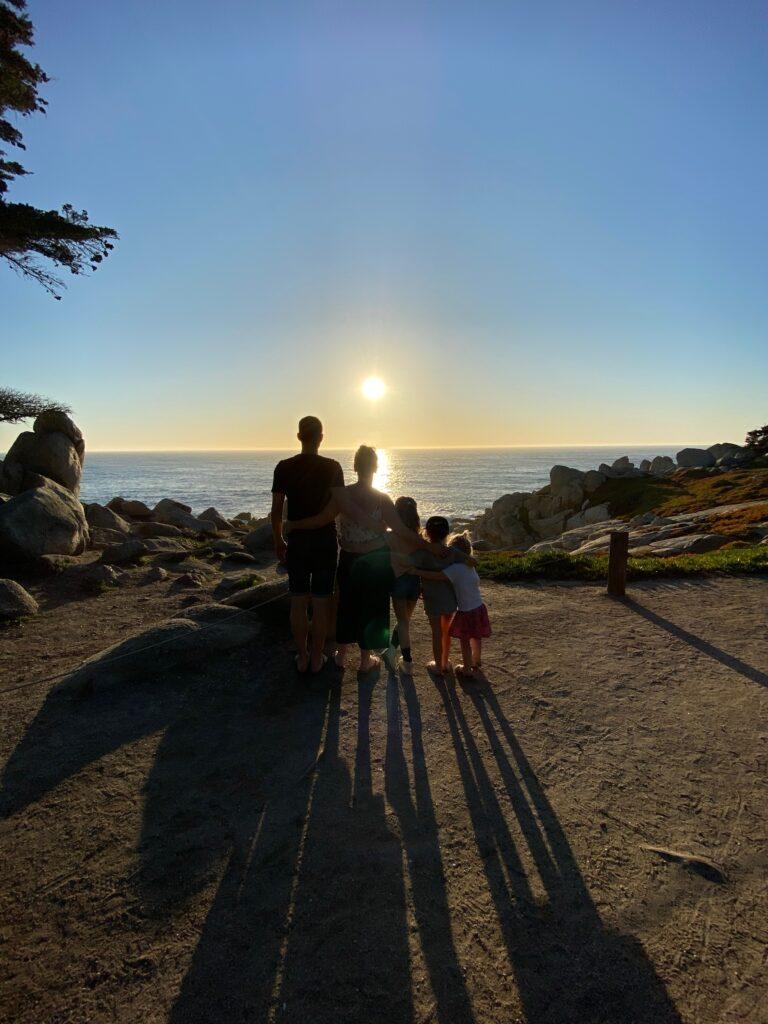 achterkant van gezin kijkend naar zonsondergang highway 1