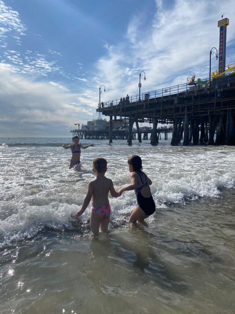 meisjes zwemmend in de oceaan aan santa monica pier